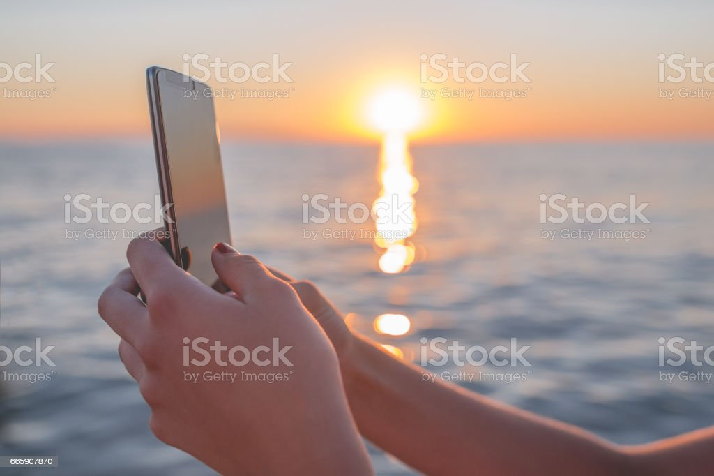 Close up of woman's hand with mobile phone on beautiful sunset background foto stock royalty-free
