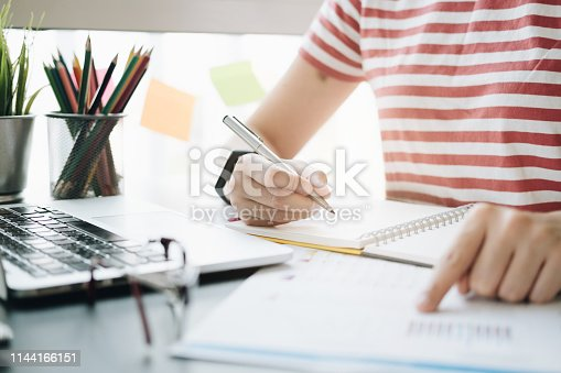 istock close up of woman's hands pointing financial report and writing in notepad. Working on project concept 1144166151