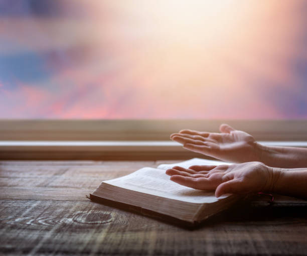 Close up of woman's hands raised in worship, reading Bible, with dramatic light. Wood table with sun rays coming through window. Christian image stock photo