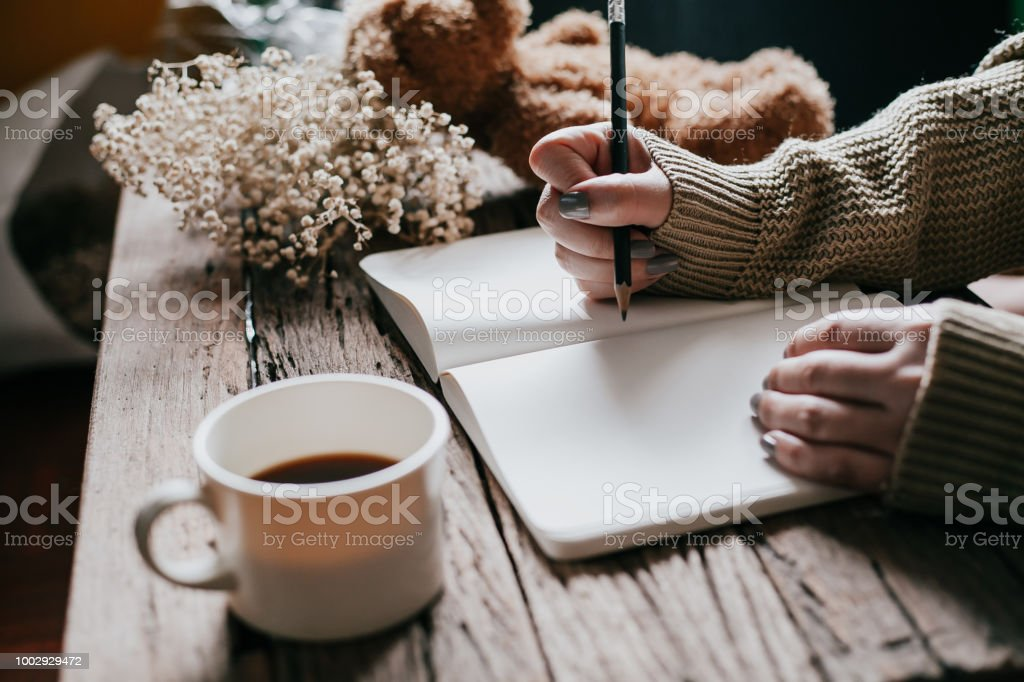 Close up of woman\'s hands writing on book, vintage color tone