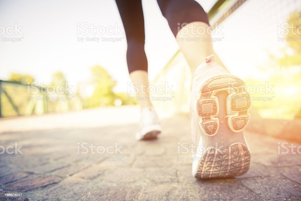 Close up of woman's running shoes on cobblestone stock photo