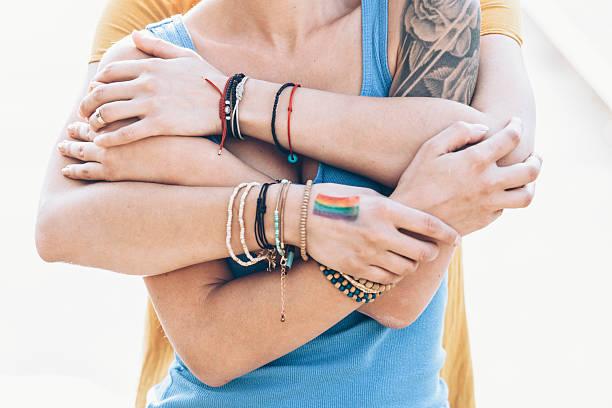 close up of women embracing on bridge - ehepaar tattoos stock-fotos und bilder