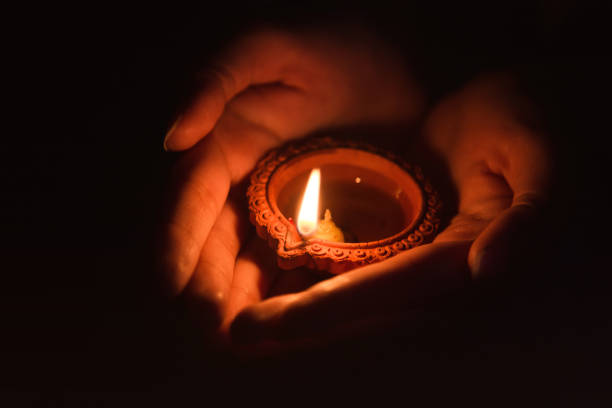 Close up of women hand holding Diwali lamp stock photo