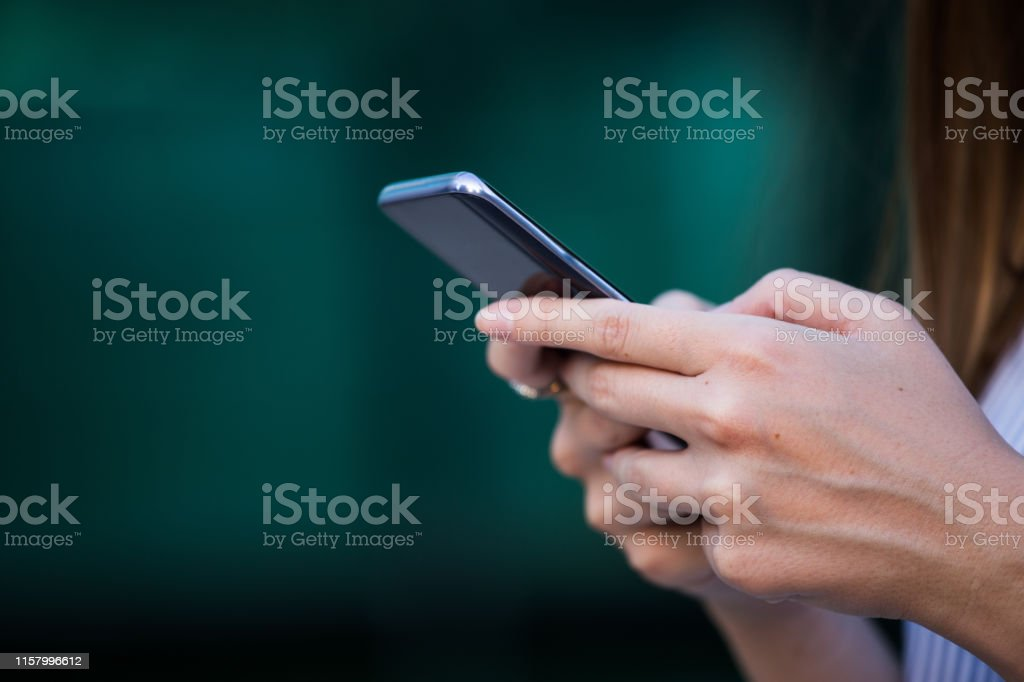 Close up of women\'s hands holding cell telephone with blank copy...