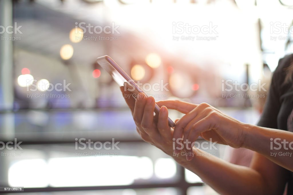 Close up of women's hands holding smartphone. Her watching sms, message, e-mail on mobile phone in coffee shop. Blurred background. stock photo