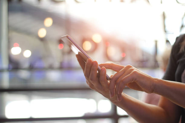 close up of women's hands holding smartphone. her watching sms, message, e-mail on mobile phone in coffee shop. blurred background. - dispositivo informatico portatile foto e immagini stock