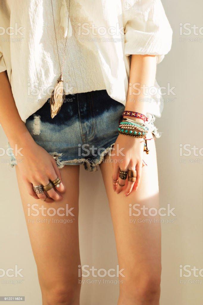Nahaufnahme der Beine und Hände im Boho-Stil in Jeans-Shorts und eine weiße Bluse Frauen – Foto