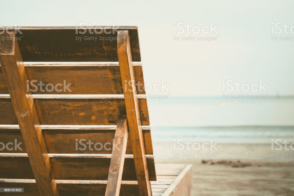 Close up of wooden chair backrest on the sandy beach stock photo