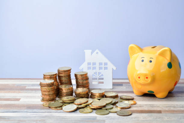 Close up of Wooden home, piggy bank and stack of money coins stock photo
