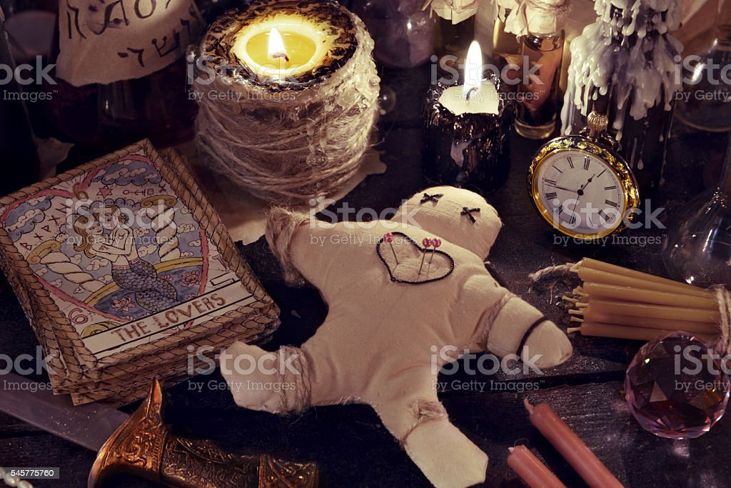 Close up of woodoo doll, knife, candles and magic objects stock photo