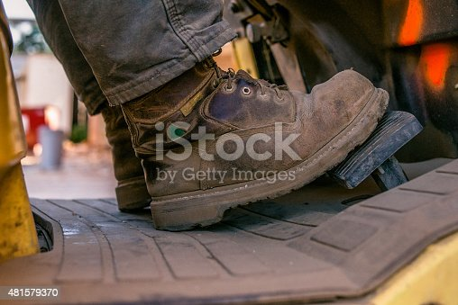 Close up of work boots of man driving forklift