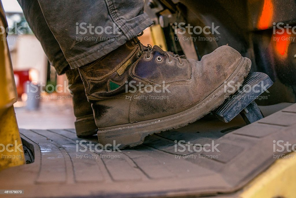 Close up of work boots of man driving forklift stock photo