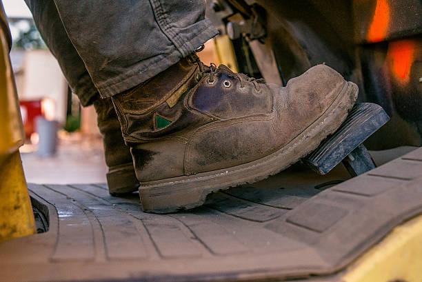 Nahaufnahme der Arbeitsstiefel of man driving Gabelstapler – Foto