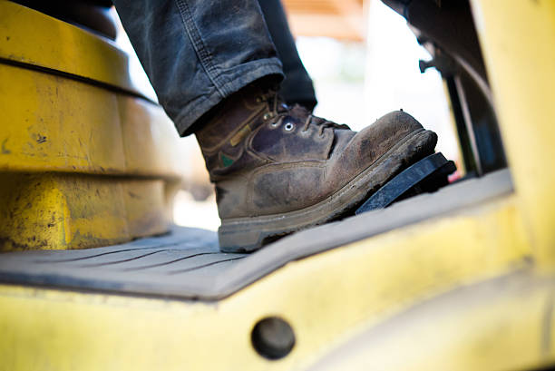 close up of workboots of man driving forklift - dirty shoes stock photos and pictures