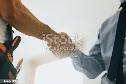 961745166istockphoto Close up of worker and architect shaking hands at construction site. 1135304692