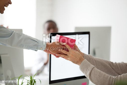 istock Close up of worker congratulating colleague with birthday with present 974191970