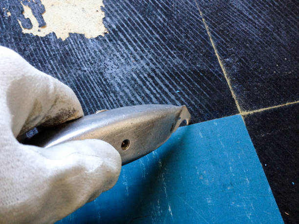 nahaufnahme des arbeitnehmers bodenbelag entfernen - fliesenkleber stock-fotos und bilder