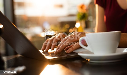 Close up of typing on computer at sunset.