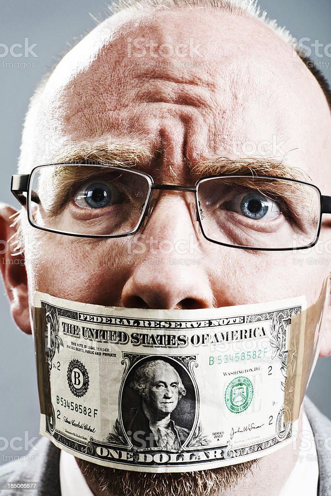 Close up of worried businessman wearing dollar bill as gag stock photo