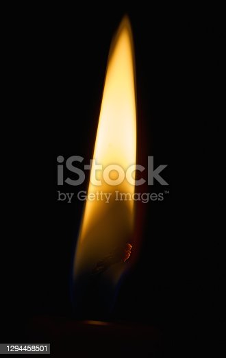 Close up of yellow candle flame on the black glowing wick of dark red candle