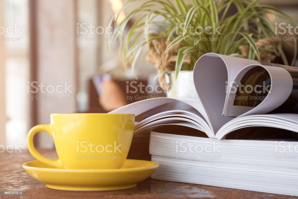 Close up of yellow coffee cup placing together with magazine like Heart Shape zbiór zdjęć royalty-free