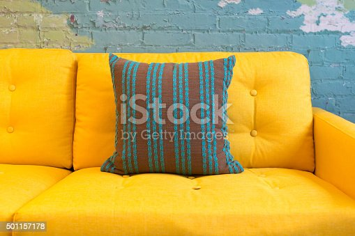 Close up of yellow fabric sofa and cushions with vintage style against blue bricks wall.