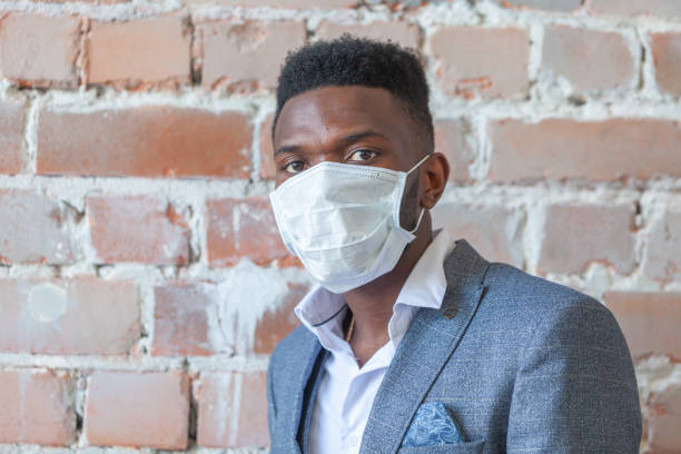 Close up of young African black man in a suit against a red brick wall is afraid of a coronavirus epidemic and wears a medical mask so as not to get infected COVID-19 stock photo