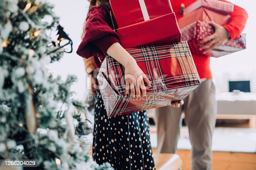 Close up of young Asian woman and man at the back holding a pile of wrapped Christmas presents standing next to Christmas tree preparing for a Christmas party