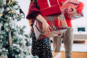 istock Close up of young Asian woman and man at the back holding a pile of wrapped Christmas presents standing next to Christmas tree preparing for a Christmas party 1266204029