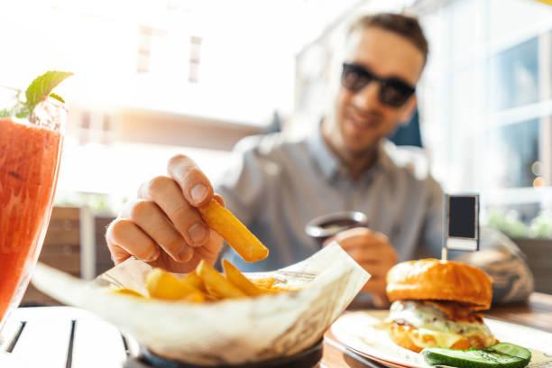 feche de atraente jovem comendo batatas fritas e hambúrguer no café de rua. - junk food - fotografias e filmes do acervo