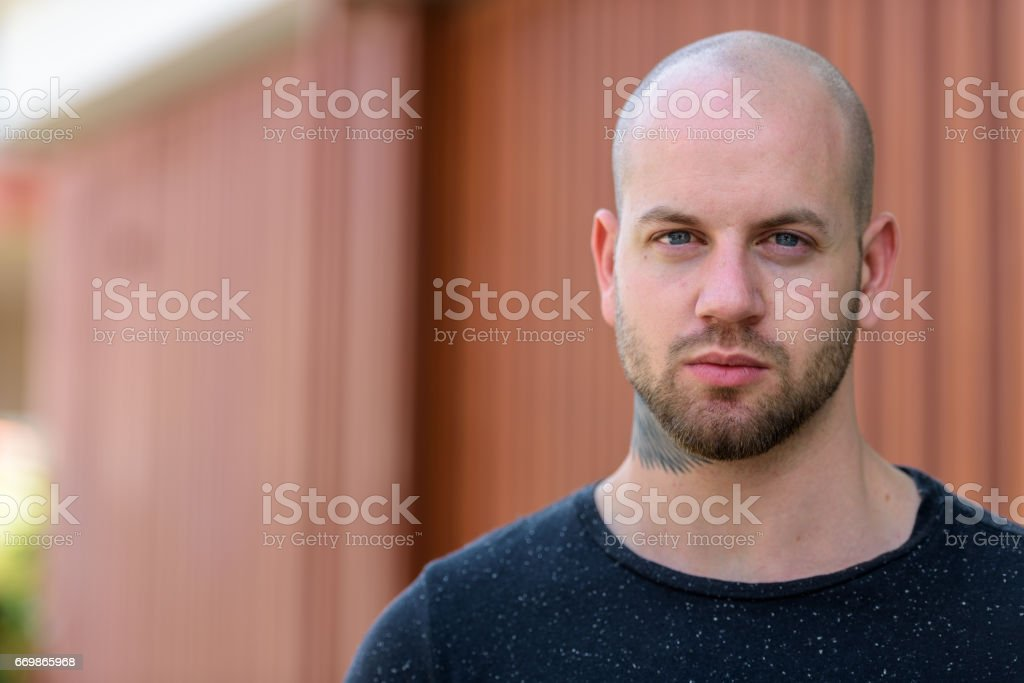 Close up of young bald muscular man with tattoos outdoors stock photo