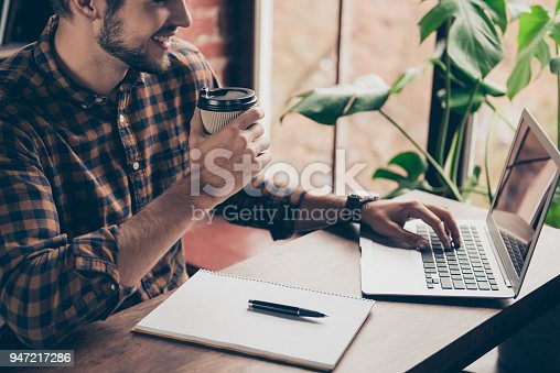 istock Close up of young bearded  manager working with laptop and drinking coffee 947217286