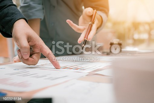 885956164istockphoto Close up of young business people group analysis to data paper chart on desk at working space. 1022015134