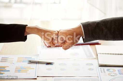 Close up of young businessman and businesswoman making a fist bump on document background; Business people wear suit with fist pump together after good deal; Business success and teamwork concept