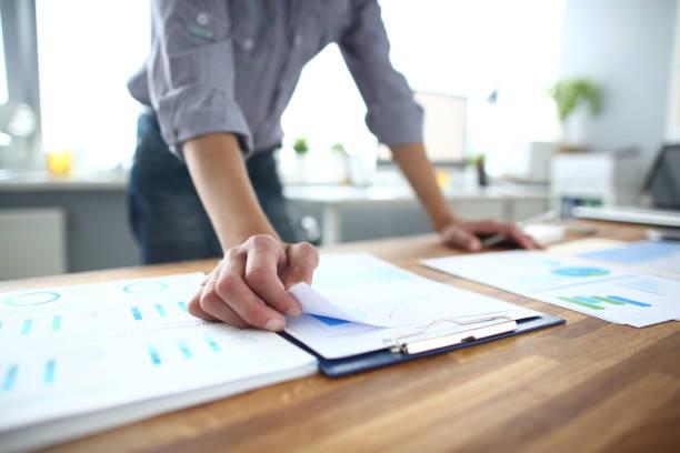 Nahaufnahme des jungen Geschäftsmannes, der Papiere mit Finanzinformationen hält, Dokumente bearbeitet, Marketingstrategien erläutert oder das Wirtschaftswachstum von Unternehmen beim Brainstorming-Meeting im Büro plant. – Foto