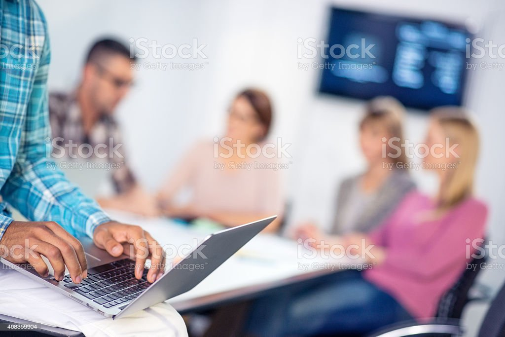 Close Up of Young Businessman Using Laptop During Board Meeting royalty-free stock photo