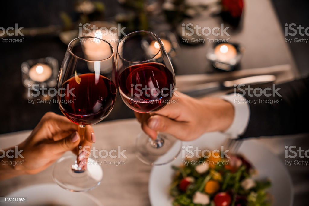 Close up of young couple toasting with glasses of red wine at restaurant Couple, Romantic, Dinner, Togetherness, Holiday Adult Stock Photo