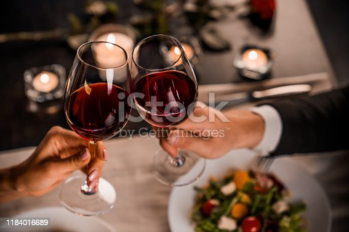 istock Close up of young couple toasting with glasses of red wine at restaurant 1184016689