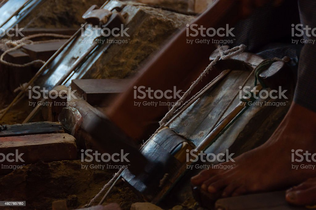 Close up of Young craftsman punching gold with a hammer stock photo