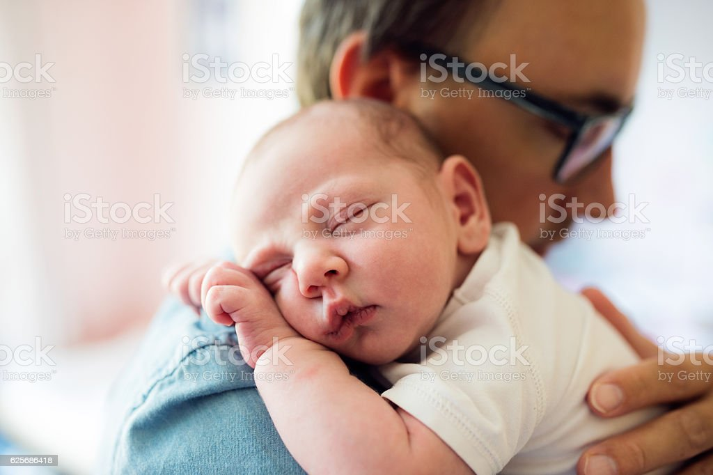 Close up of young father holding his newborn baby son - foto de acervo