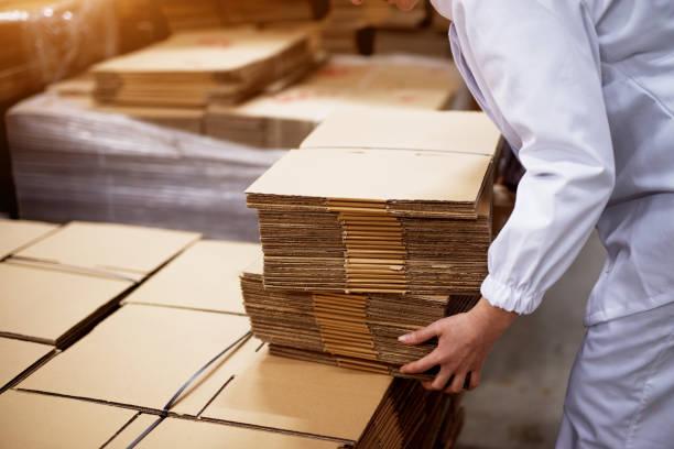 nahaufnahme von junge arbeitnehmerin abholung stapeln von gefalteten kartons aus einem größeren stapel in fabrik-lagerraum. - box falten stock-fotos und bilder