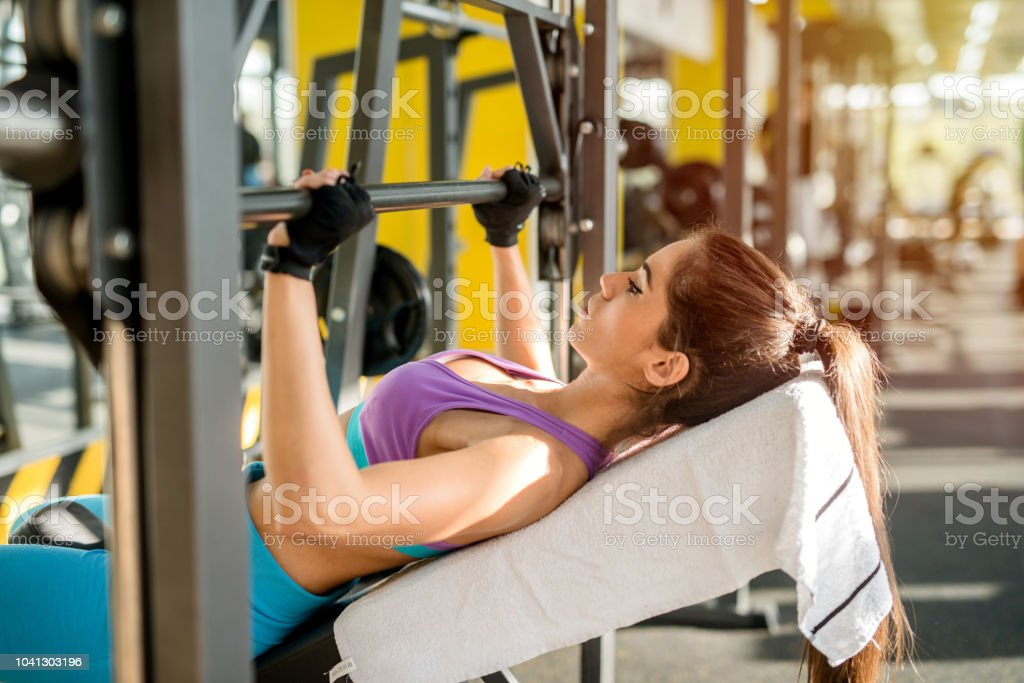 Close up of young fit girl holding weight in her arms. Gym training in bright gym. stock photo
