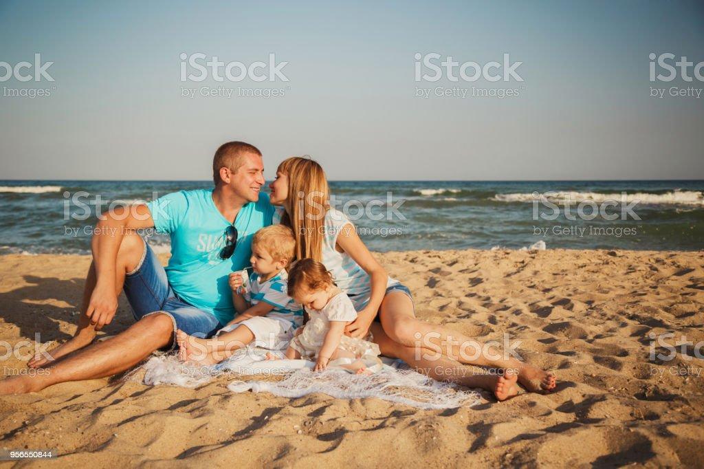 Nahaufnahme eines jungen glücklich liebevolle Familie mit kleinen Kindern in der Mitte, gemeinsam Spaß haben am Strand in der Nähe des Ozeans, Familie glücklich Lifestyle-Konzept - Lizenzfrei Bewegung Stock-Foto