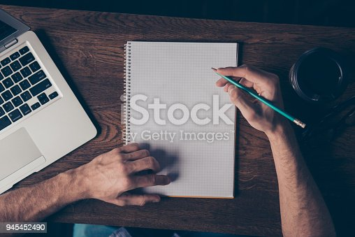 istock Close up of young man drawing scheme in his notebook 945452490