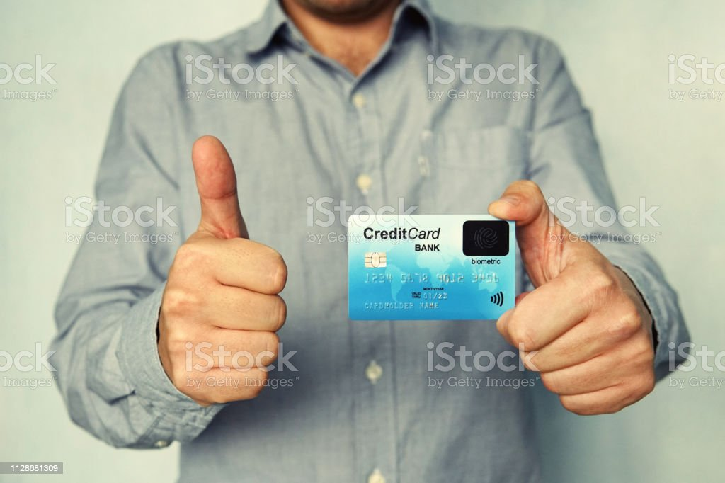 Close up of young man in shirt holding credit card with biometric technology and showing thumb up. Man is glad to use bank card of new type. Advantages of using banking. Biometric payment card. Sign. stock photo