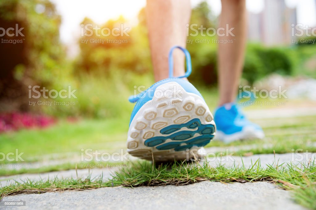 Close up of young man jogging outdoors stock photo