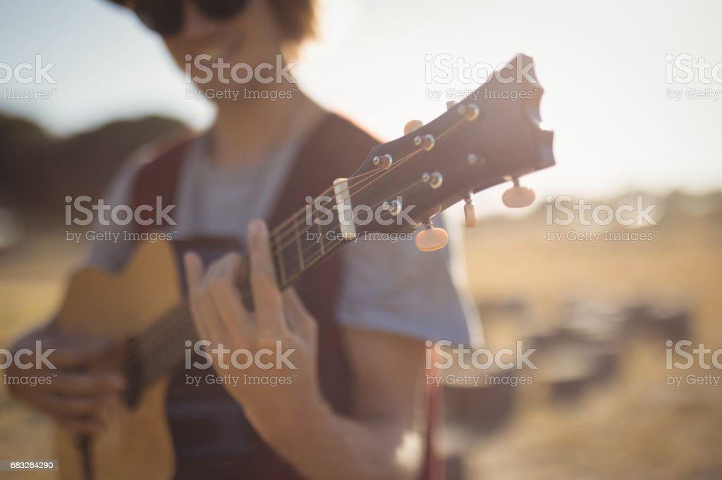 Nahaufnahme von junger Mann spielt Gitarre im stehen auf Feld Lizenzfreies stock-foto