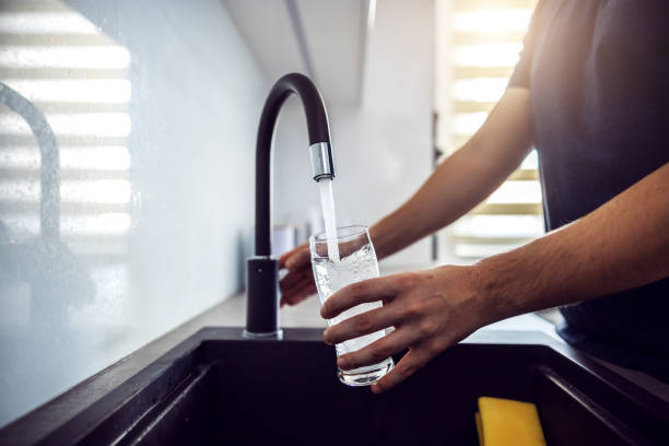 Close up of young man pouring fresh water from kitchen sink. Home interior. stock photo