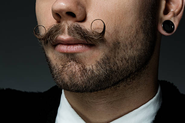 close up of young man with long moustaches close up of young man with long moustaches mustache stock pictures, royalty-free photos & images