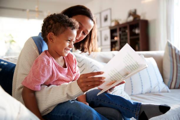 närbild på ung mamma sitter på en soffa i vardagsrummet en bok med hennes barn son, som sitter på hennes knä, sidovy - förälder bildbanksfoton och bilder